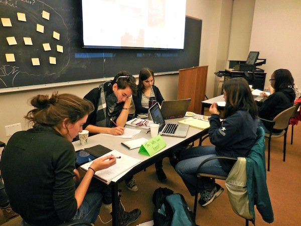 Four female students huddle around a table to write on their laptops in a Trotter Hall classroom. In the background: yellow sticky notes are clustered on the black chalkboard.