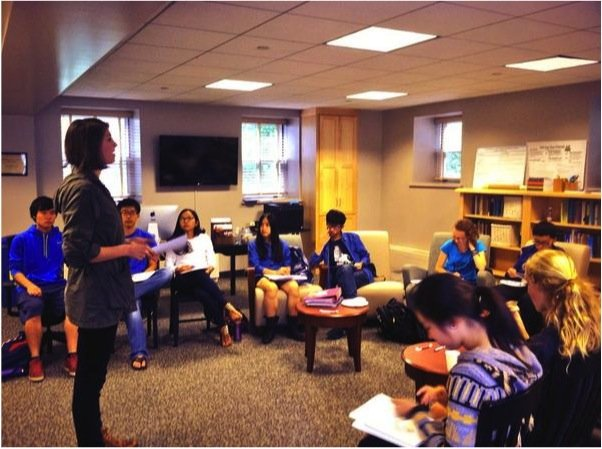 WA Julia Carleton '15 stands before a group of students discussing pre-writing strategies at a workshop hosted by the Writing Associates