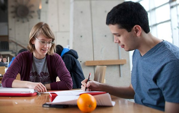 This image shows two Writing Associates discussing a paper