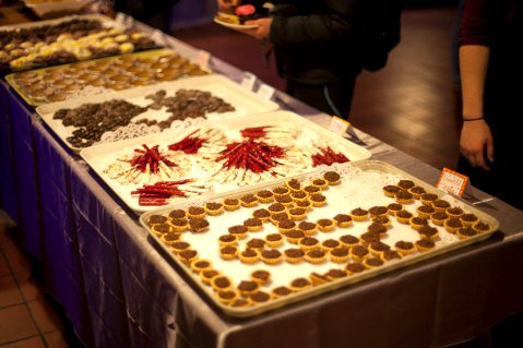 Students admire the food selection, including Treacle Tarts displayed in the shape of the Deathly Hallows