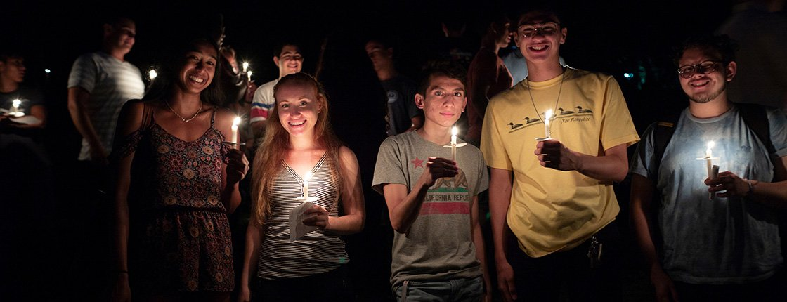 Student hold candles at first collection