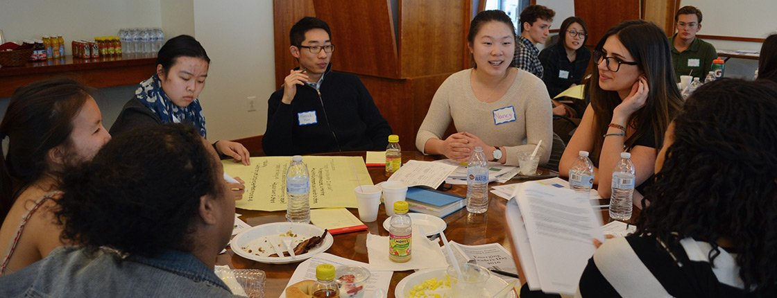 Students engage with one another around a table during a student leadership workshop