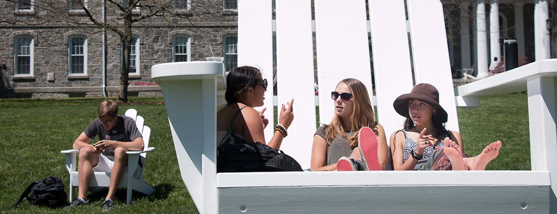 Students sit in the big chair on Parrish Beach