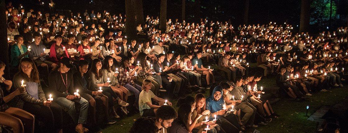 The Class of 2021 holds lit candles in the Scott Amphitheater at night