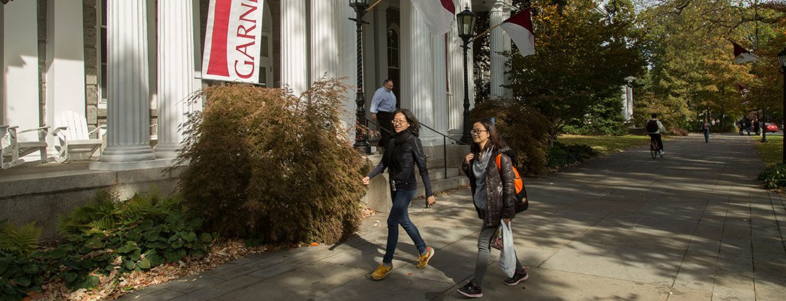 Two students walk past Garnet Weekend signs on Swarthmore's campus