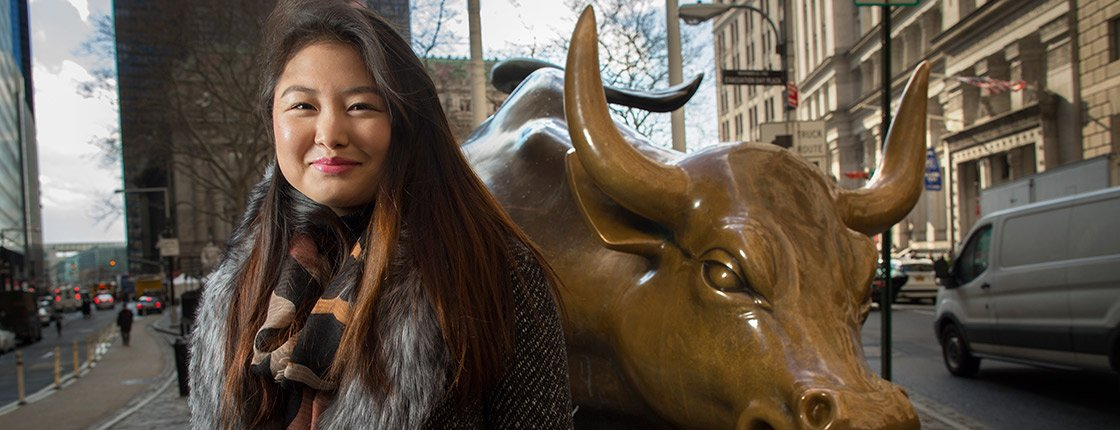 Christine Kim '17 stands next to the Wall Street Bull statue