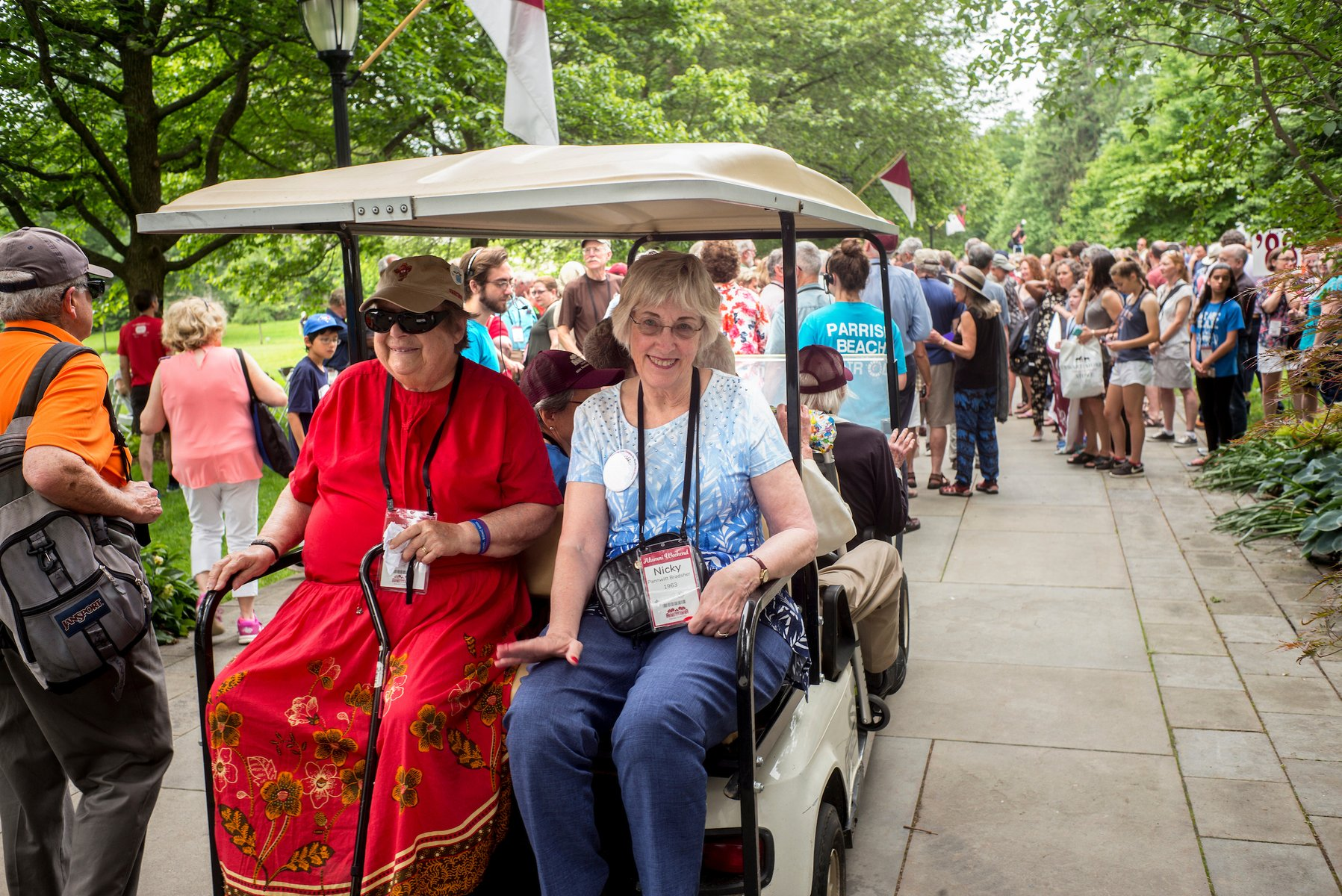 Alumni ride on a golf cart during the Parade of Classes