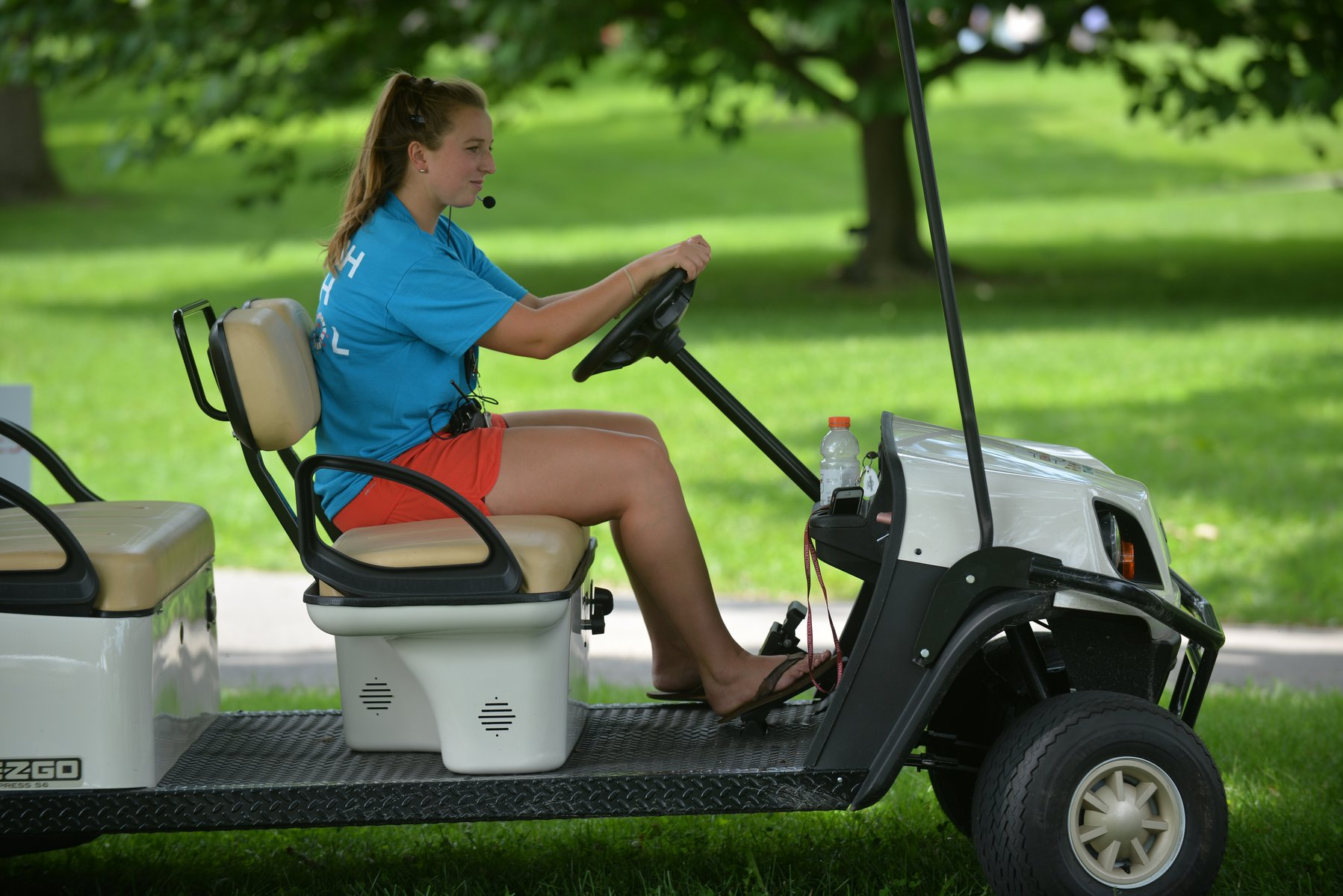 A student work drives a golf cart