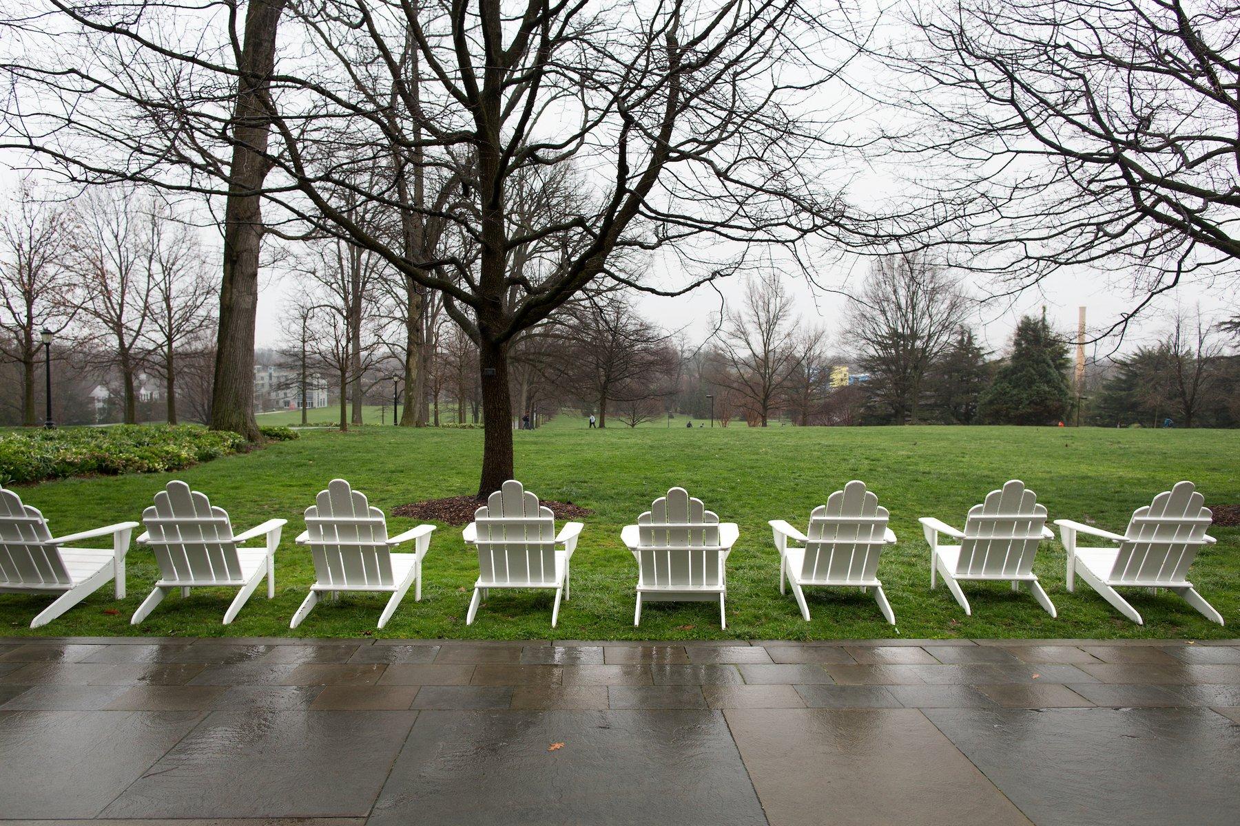 A row of empty Adirondack chairs on Parrish Beeach