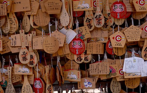 Several dozen wood pattels with oriental writing and designs hanging in a shop