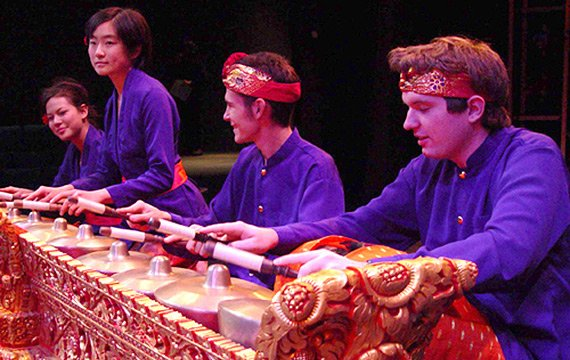 Men and women dressed in purple and red playing percussion bells which are sitting in an ornate red and silver table