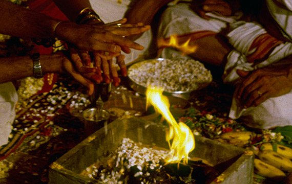 Group of people sitting cross-legged on rugs, preparing food over open flame