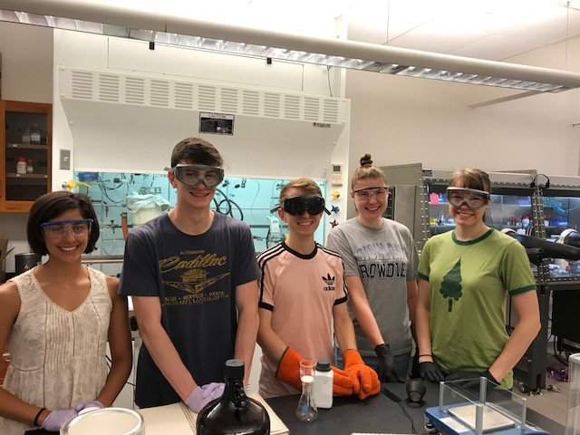 The group standing in front of a fumehood in the lab.
