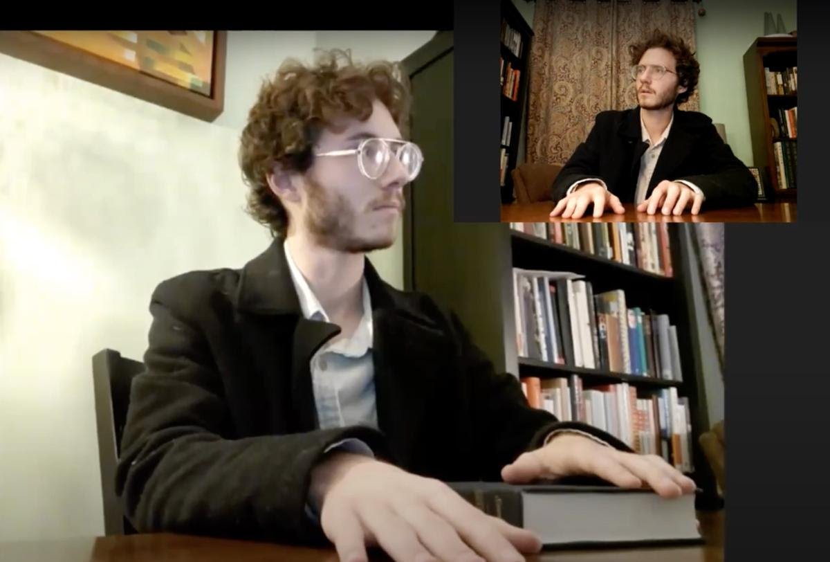 A light-skinned person with short hair and glasses wearing a suit jacket and sitting in front of a bookshelf looking to the right. A small inset image shows the same person from another angle.