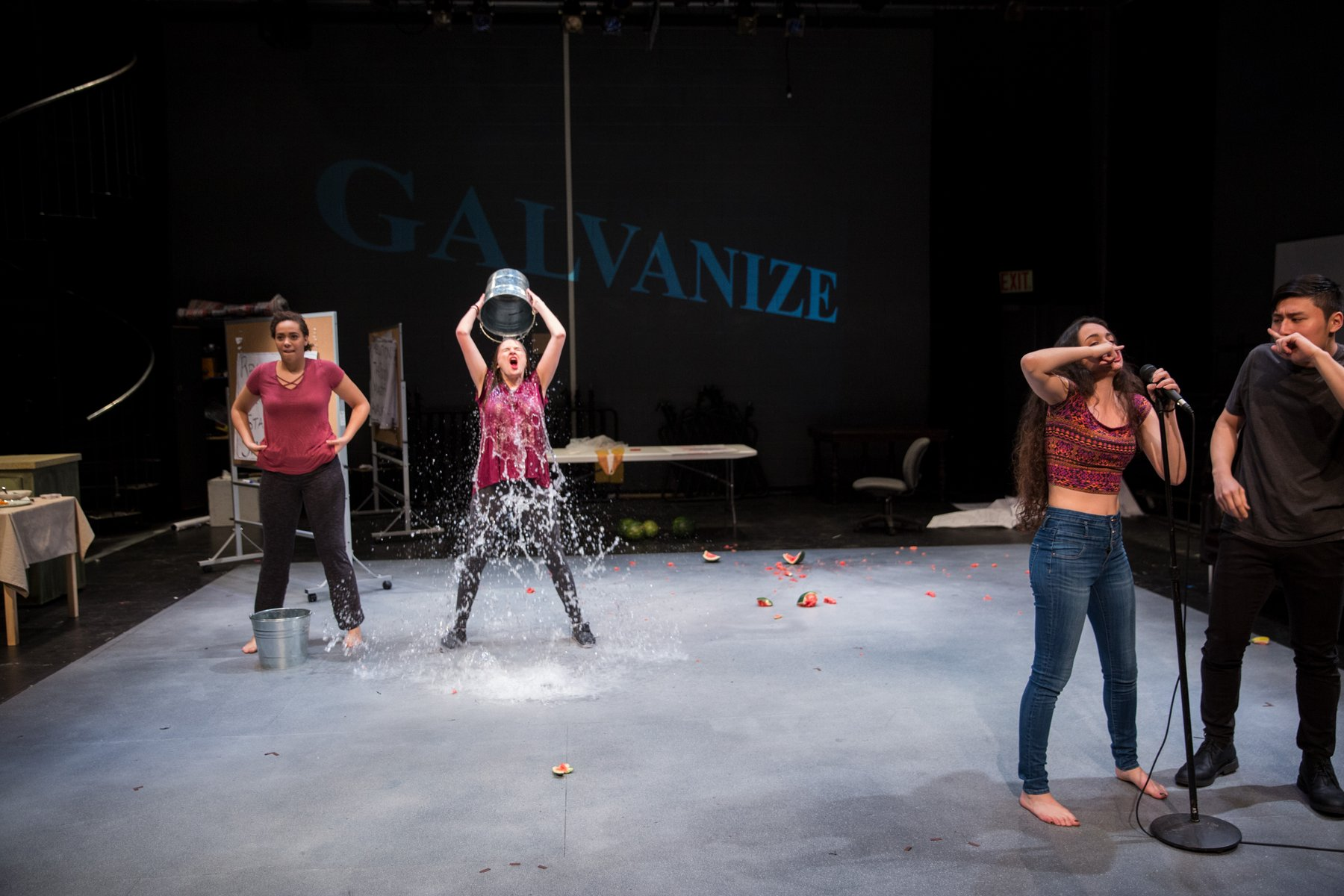 Four actors on a bare stage in contemporary clothing, two in the foreground at a microphone, and two in the background dumping a bucket of water on their heads.