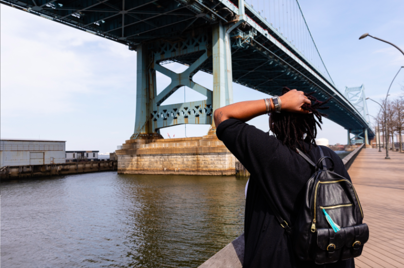 A person with dreadlocks and a backpack stands with their back to the camera and a hand on their head, looking up at the Benjamin Franklin Bridge.