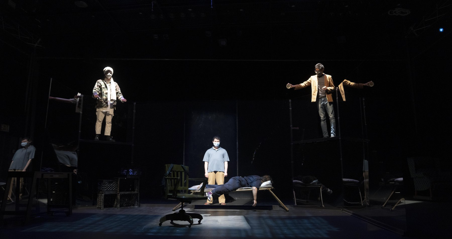 A dark stage with spotlights on four actors - one lying face down and three standing above.
