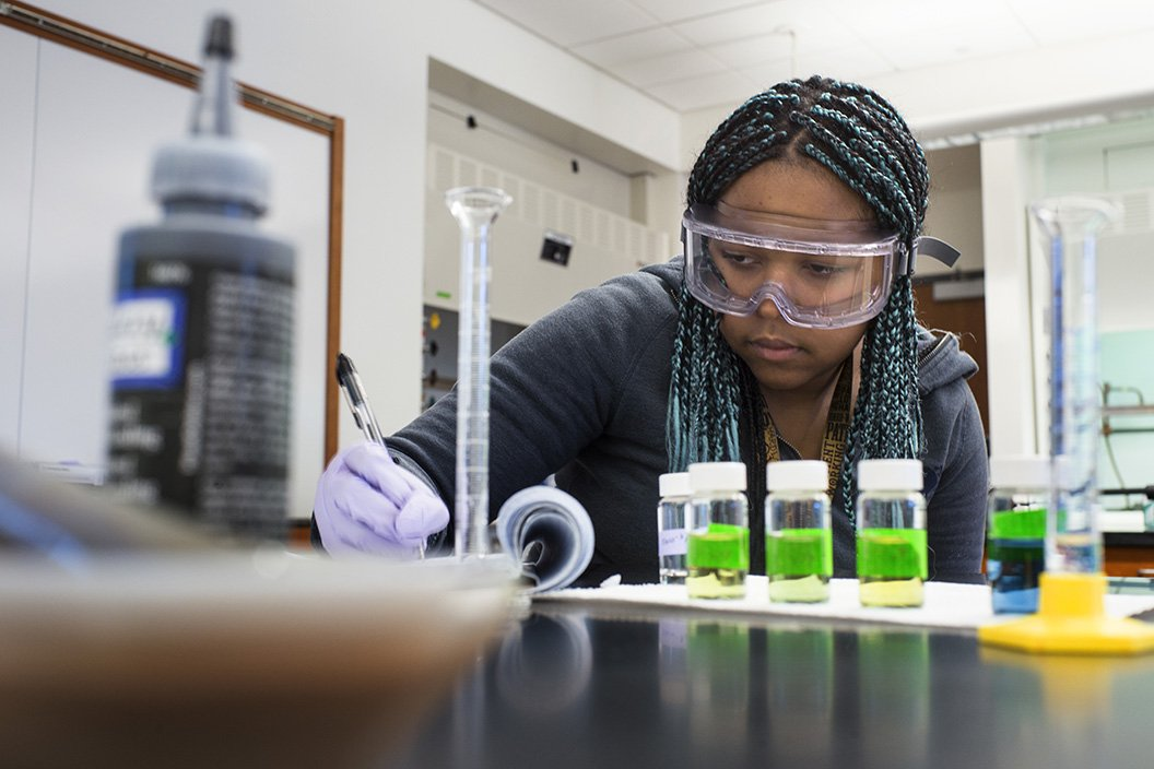Student in chemistry lab with vials of green liquid