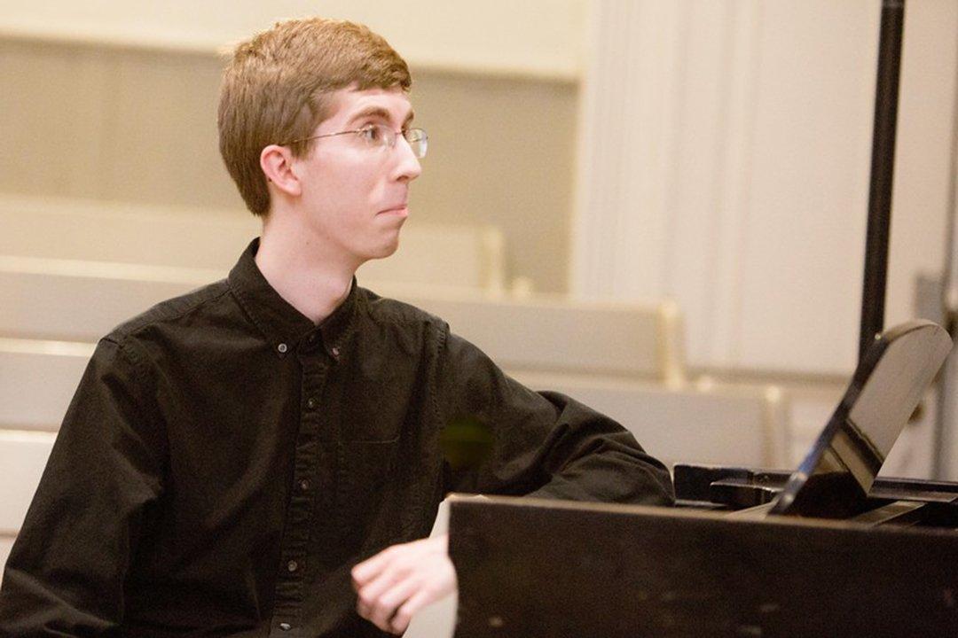 Student wearing glasses and black shirt sits at piano