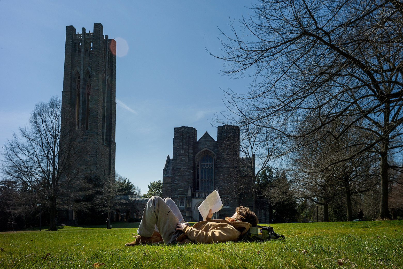 Student lies on ground and reads book outdoors