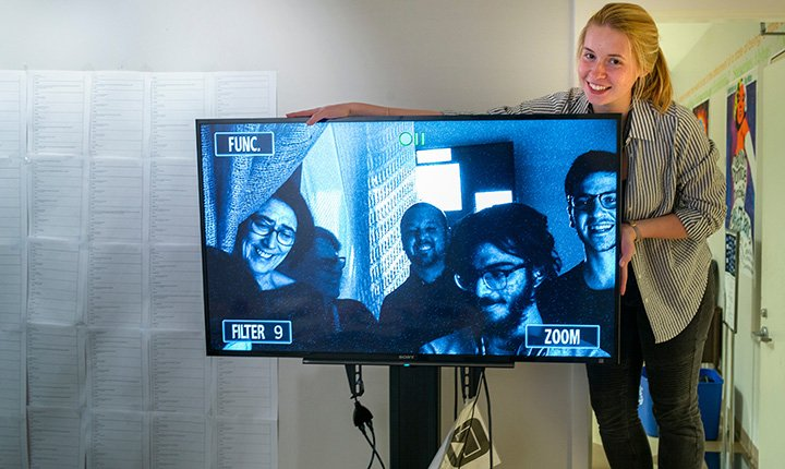 Student poses with TV monitor in exhibit