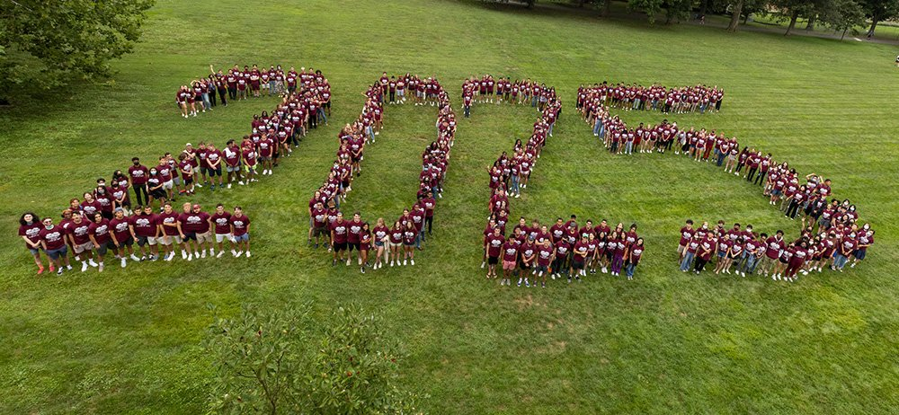 """Students spell out """"2025"""" standing outside"""