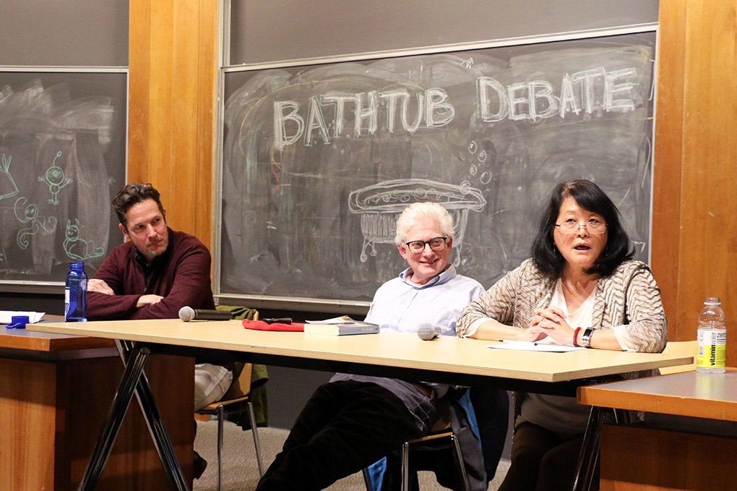 "Professors sit in front of blackboard that says ""Bathtub Debate"""