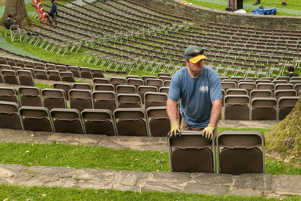 Member of the grounds department sets up chairs in Scott Amphitheater