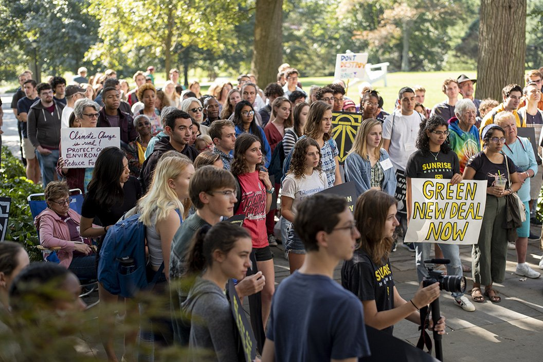 Students, faculty, staff and community members stand on Magill Walk
