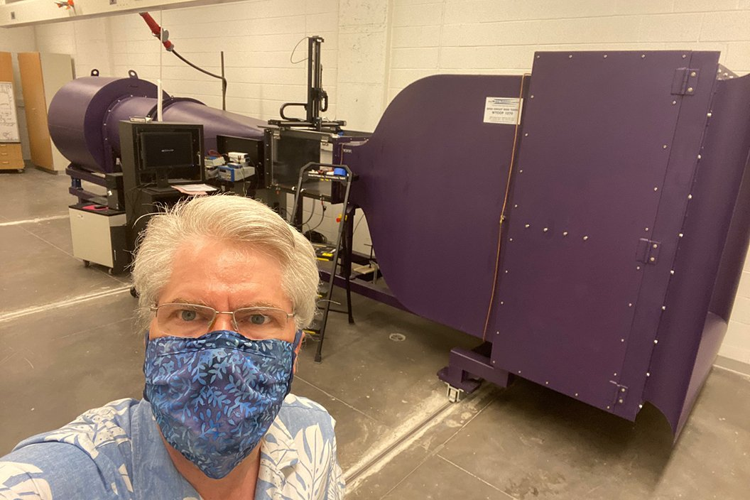 Man in mask stands indoors with wind tunnel machine in background