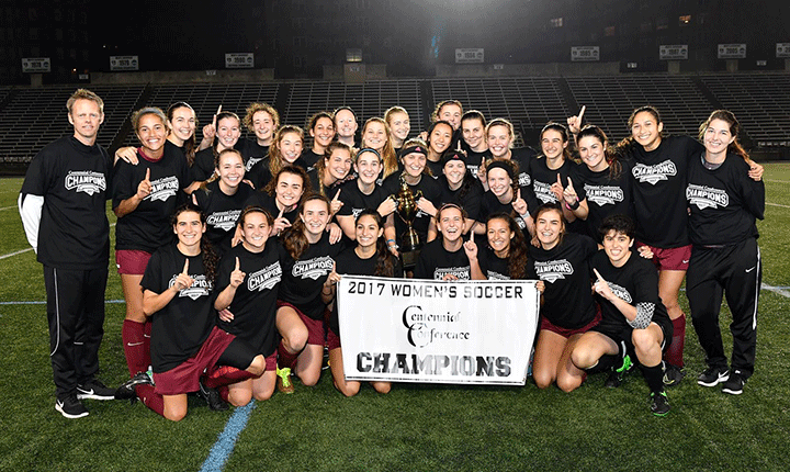 The women's soccer team poses fora photo with the Centennial Conference Championship banner