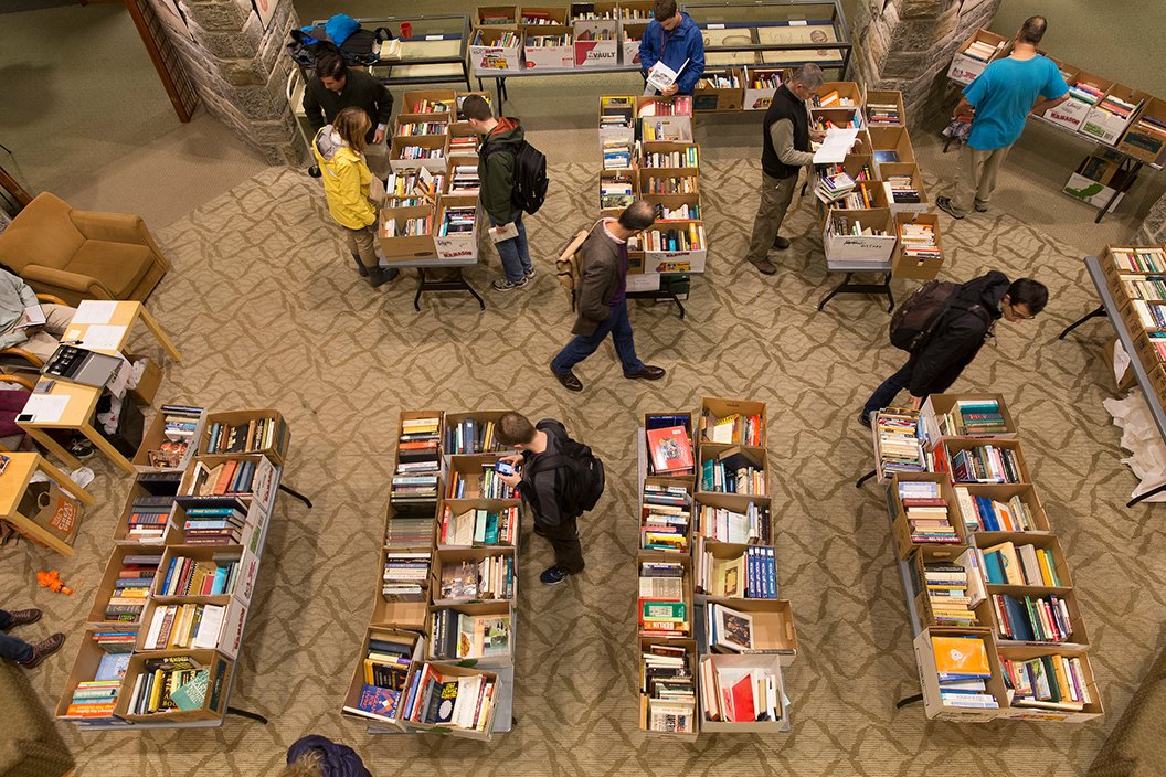 Overhead shot of people looking through table of books