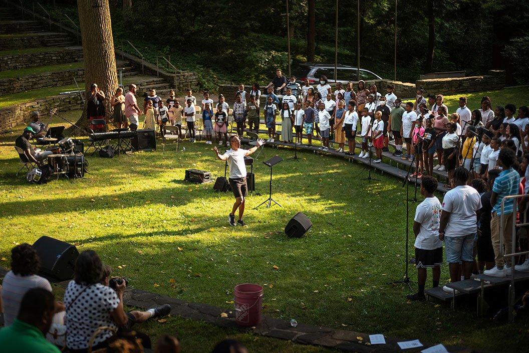Person stands in outdoor amphitheater conducting choir