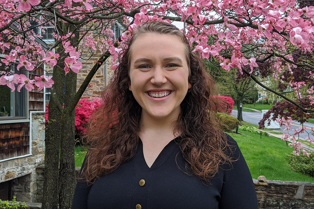 Shay Downey '22 smiling in front of tree with pink flowers and green grass.
