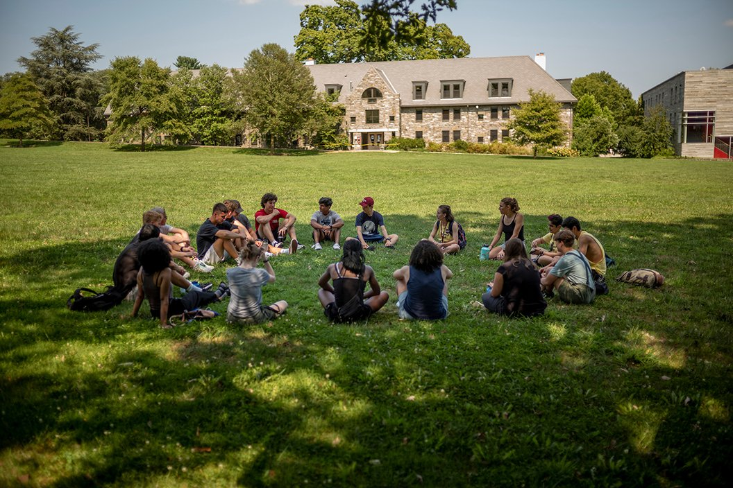 Students sit in circle on outdoor lawn