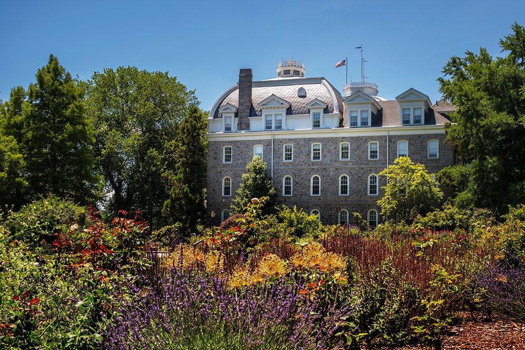 Flowers bloom in Dean Bond Rose Garden with Parrish Hall in background