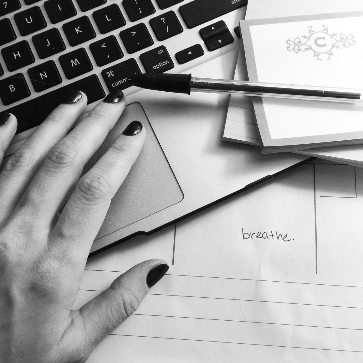 "Black and white photo of hand hovering above a keyboard with pad of paper and pen nearby and the word ""breathe"" written on the page."