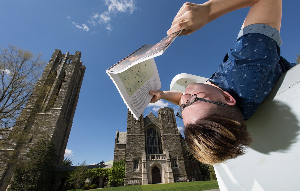 Student reading in front of Clothier Hall