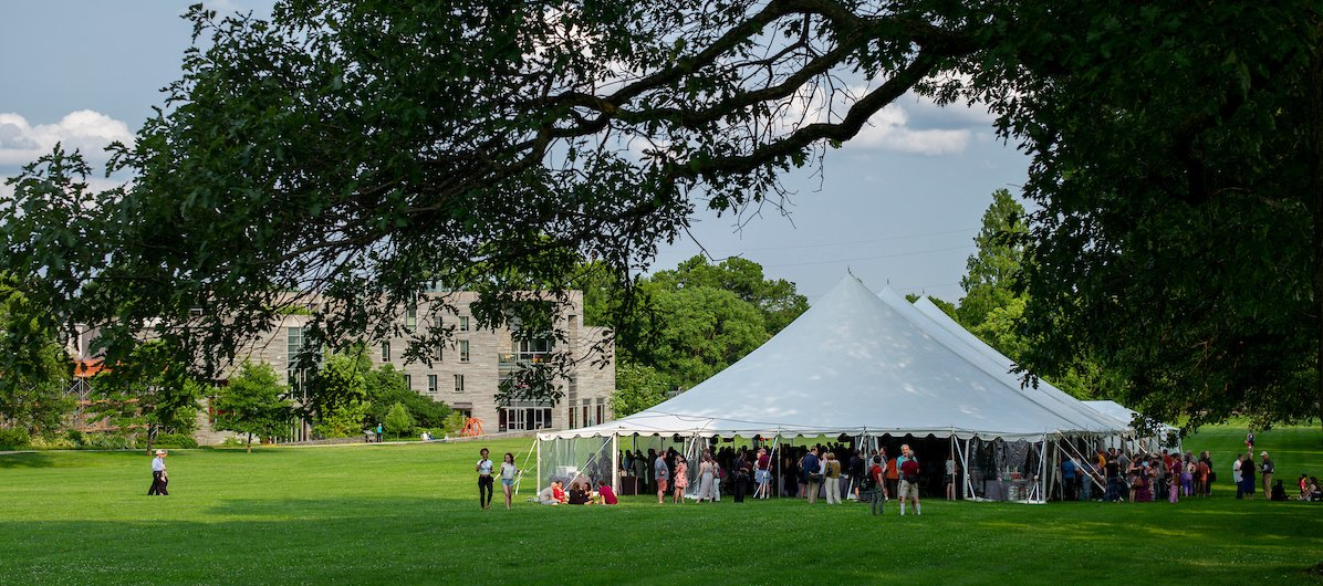 Alumni gather under a tent on Parrish Beach during Alumni Weekend 2019