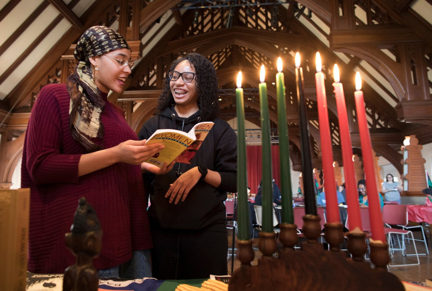 Two women lighting Kwanzaa candles