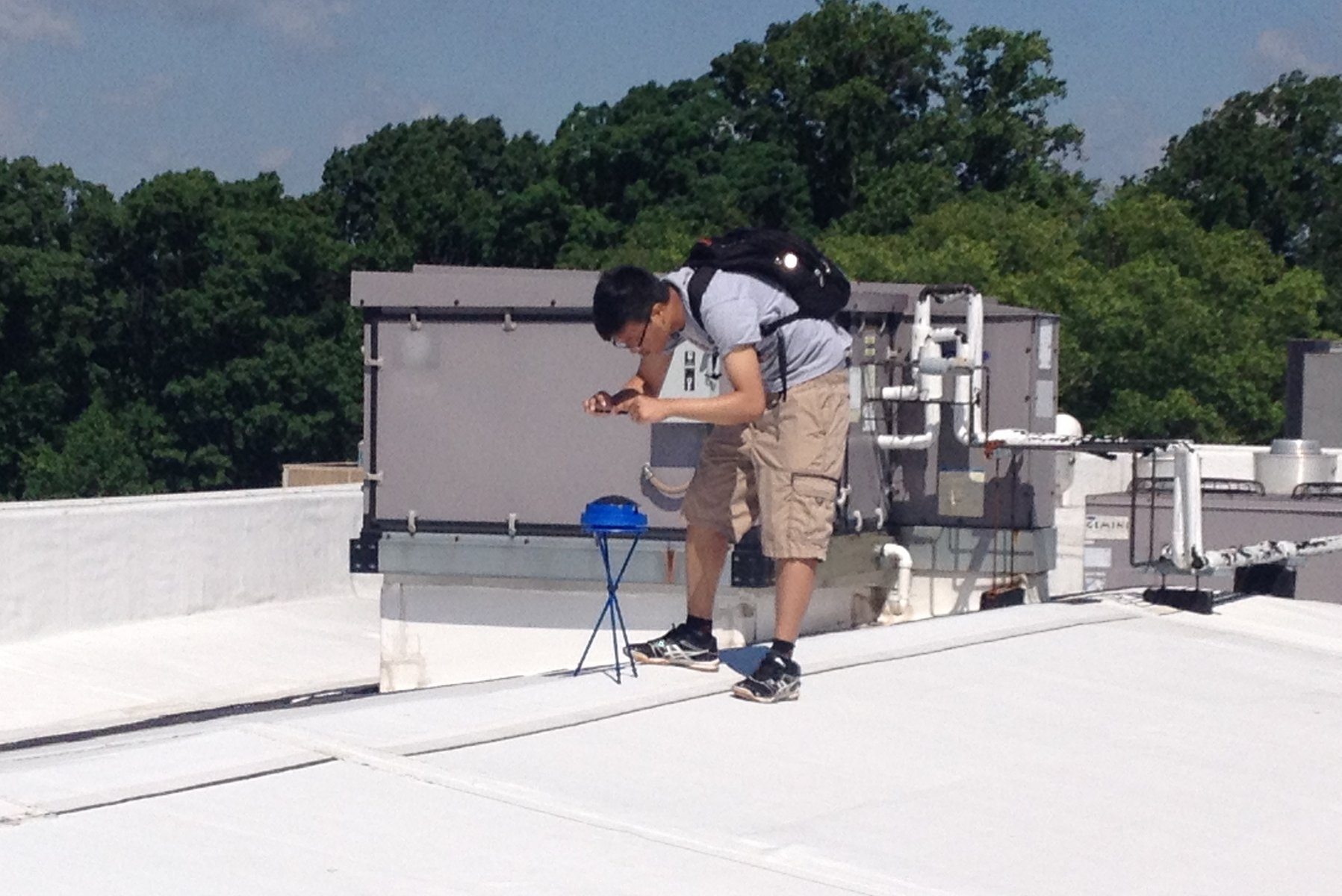 Robin Htun '18 stands on a white rooftop, bent over taking a photograph of a small blue device, a solar pathfinder. Green treetops and a blue sky are visible in the background.