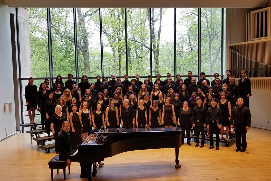 Members of chorus chorus stand on risers in front of large glass window